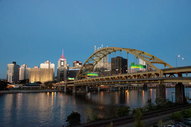 Pittsburgh dusk Pittsburgh Golden Triangle framed by the Fort Pitt Bridge at dusk. pittsburgh bridge stock pictures, royalty-free photos & images