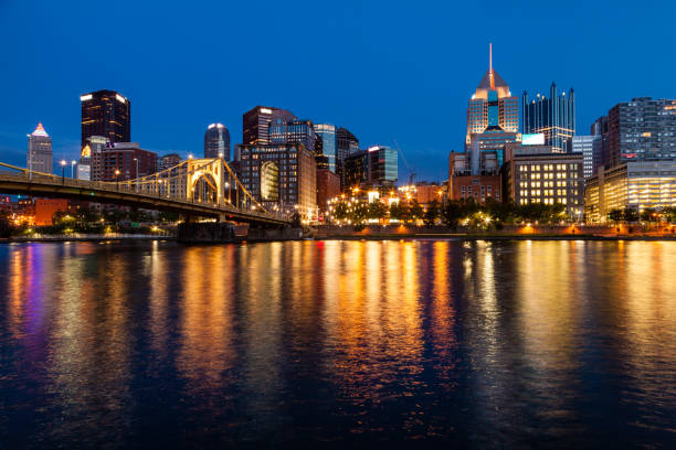 Pittsburgh skyline and the Allegheny River View of Pittsburgh skyline from the Allegheny River after sunset pittsburgh stock pictures, royalty-free photos & images