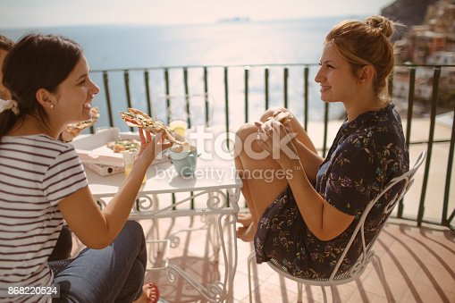 Photo of a couple of friends having Italian pizza on the terrace with a view of amazing Positano, Italy