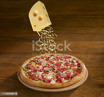 Pizza pie and grating cheese on wooden background