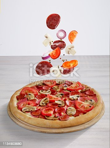 Pizza and ingredients on table top
