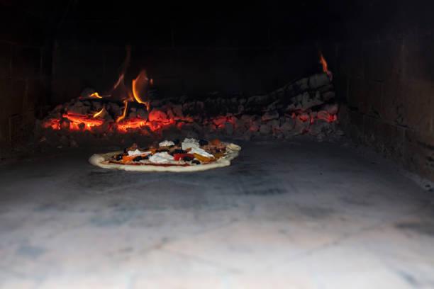 pizza backen im backofen im freien mit holzofen im hintergrund - pizzaofen garten stock-fotos und bilder