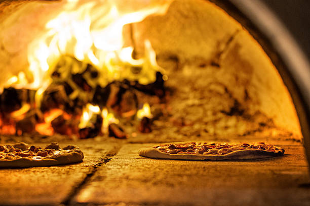 pizza baking in traditional oven - pizzeria stock photos and pictures
