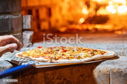 Cook cooking Pizza in a wood fire Brick oven at a pizzeria