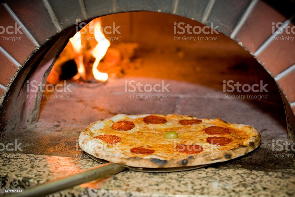 Pizza being taken out of the oven royalty-free stock photo