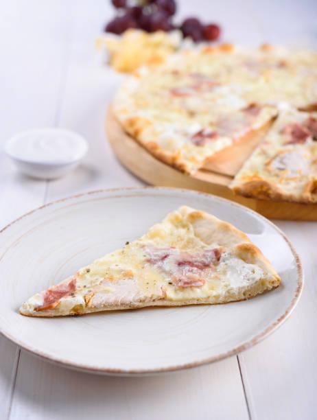 pizza bianca mit huhn, schinken und auf einem holzbrett neben einem trauben und käse-sahne-sauce - schmaler tisch stock-fotos und bilder