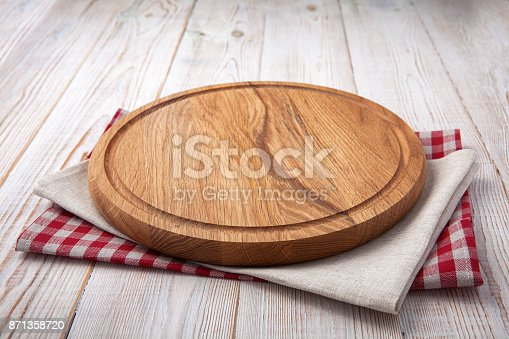 istock Pizza board with a napkin on white wooden table. Top view mock up 871358720