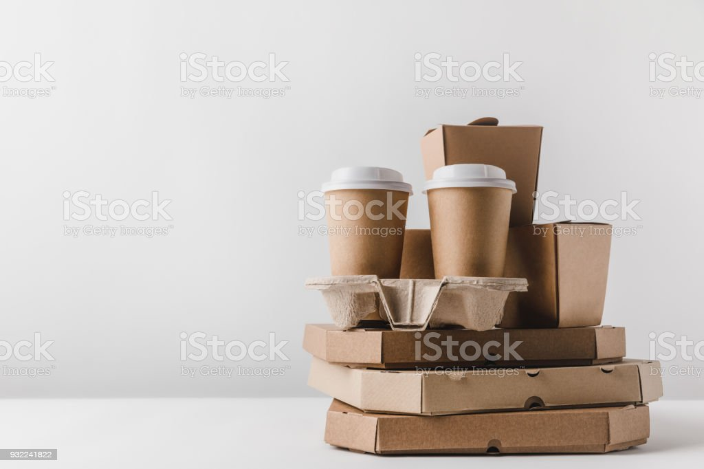 pizza boxes and disposable coffee cups with noodles boxes on table stock photo