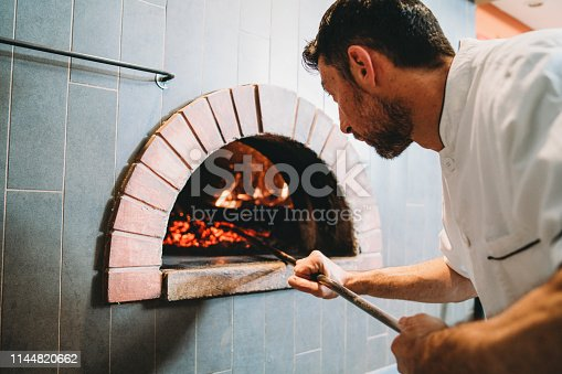 Pizza chef checking the oven of his pizzeria