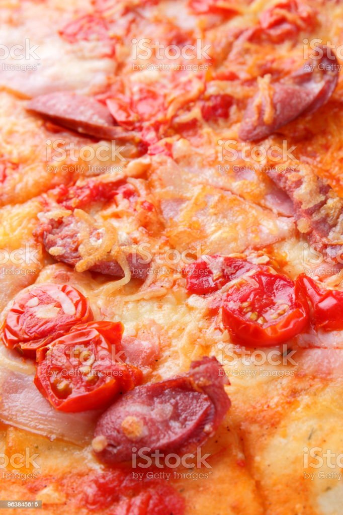 Pizza close-up, Italian pizza with bacon, tomatoes, sausages and cheese, appetizing pastry top view, baked cheese cake with meat, delicious lunch, designer's preparation - Royalty-free Backgrounds Stock Photo