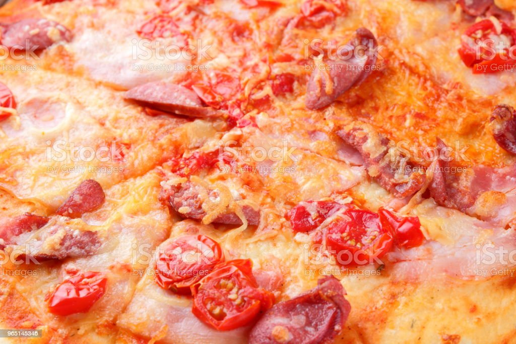 Pizza close-up, Italian pizza with bacon, tomatoes, sausages and cheese, appetizing pastry top view, baked cheese cake with meat, delicious lunch royalty-free stock photo