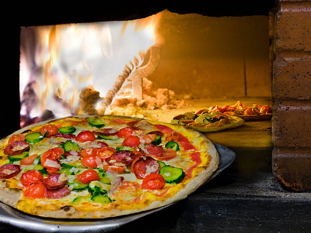 pizza coming out of a wood burning oven. stock photo