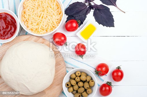 1136817041 istock photo Pizza cooking background with dough, vegetables and spices. Ingredients for cooking pizza - tomatoes, olive oil, dough, basil, ketchup and olive.Top view 692553240