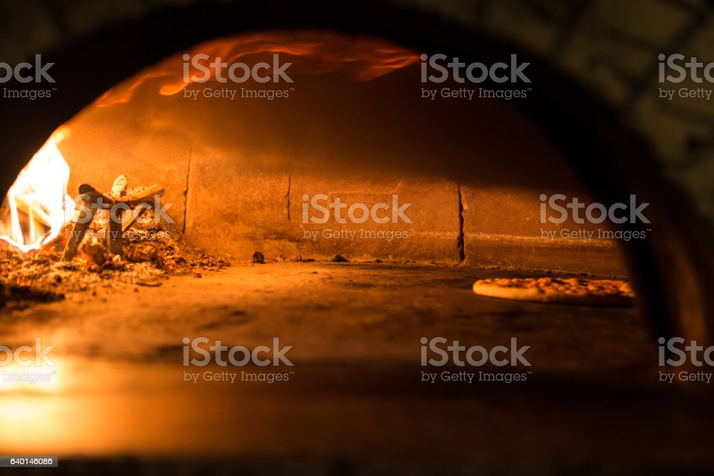 Pizza cooking in a tradition oven stock photo