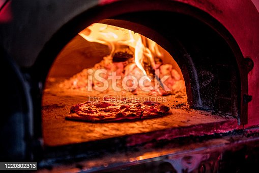 a Single pizza is busy cooking inside a pizza oven with the flames burning in the back ground.