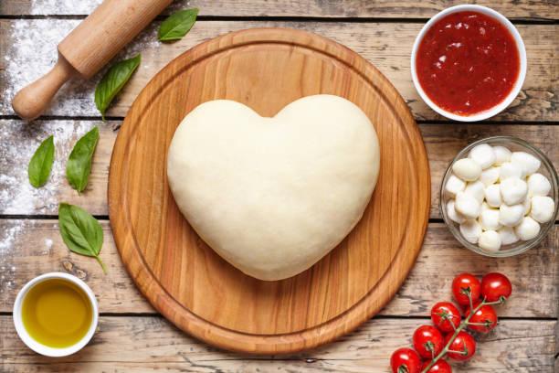 pizza kochen zutaten. kochen mit liebe. teig in herz-form-draufsicht. backzutaten auf dem holztisch: teig, mozzarella, tomaten, basilikum, olivenöl, käse, sauce, gewürze. - low carb pizzateig stock-fotos und bilder