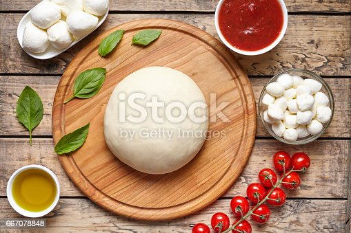 1136817041 istock photo Pizza cooking ingredients. Dough, mozzarella, tomatoes, basil, olive oil, spices. Work with the dough. Top view. Flat lay. Traditional italian pizza margherita. 667078848