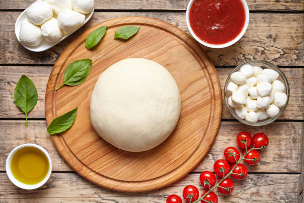 Pizza cooking ingredients. Dough, mozzarella, tomatoes, basil, olive oil, spices. Work with the dough. Top view. Flat lay. Traditional italian pizza margherita. stock photo