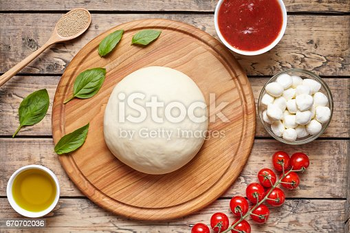 1136817041 istock photo Pizza cooking ingredients on cutting board. Dough, mozzarella, tomatoes, basil, olive oil, spices. Work with the dough. Top view. Flat lay. Traditional italian pizza margherita. 670702036