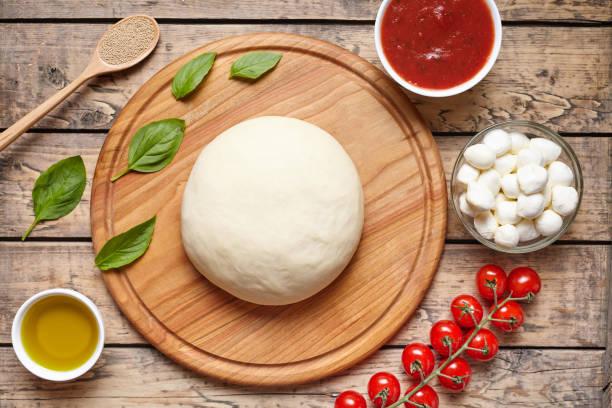 pizza kochen zutaten auf schneidebrett. teig, mozzarella, tomaten, basilikum, olivenöl, gewürze. arbeiten sie mit dem teig. ansicht von oben. flach zu legen. traditionelle italienische pizza margherita. - low carb pizzateig stock-fotos und bilder