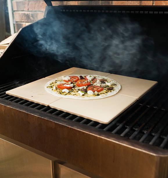 pizza kochen am grill - grillstein stock-fotos und bilder