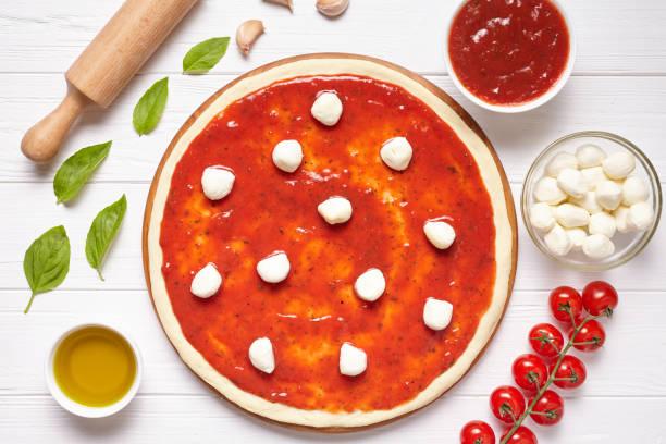 pizza vorbereitung kochzutaten. backzutaten auf dem weißen holztisch: teig, mozzarella, tomaten-sauce, basilikum, olivenöl, tomaten. italienische küche küche pizza margarita - low carb pizzateig stock-fotos und bilder