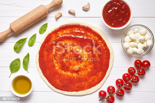 1136817041 istock photo Pizza cooking preparation. Raw pizza dough with baking ingredients: tomatoes sauce, mozzarella, basil, olive oil, cheese, spices.Italian food cuisine background. Flat lay. 667079424