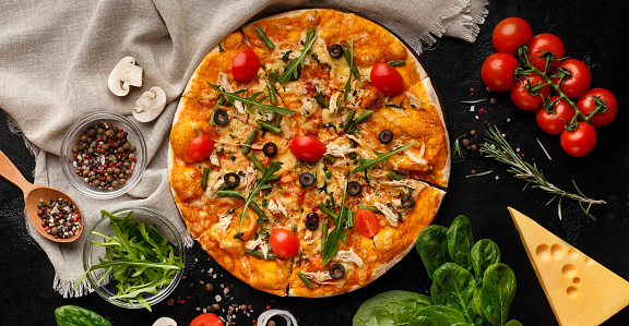 Pizza decorated with rocket salad and cherry tomatoes