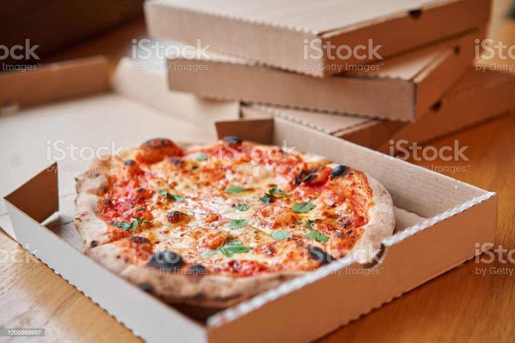 Pizza delivery concept. Baked products in a cardboard box against a wooden background. Baked tasty margherita pizza in Traditional wood oven in Neapolitan restaurant, Italy. Pizza delivery concept. Baked products in a cardboard box against a wooden background. Baked tasty margherita pizza in Traditional wood oven in Neapolitan restaurant, Italy Backgrounds Stock Photo