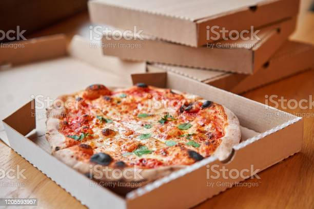 Pizza Delivery Concept Baked Products In A Cardboard Box Against A Wooden Background Baked Tasty Margherita Pizza In Traditional Wood Oven In Neapolitan Restaurant Italy Stock Photo - Download Image Now
