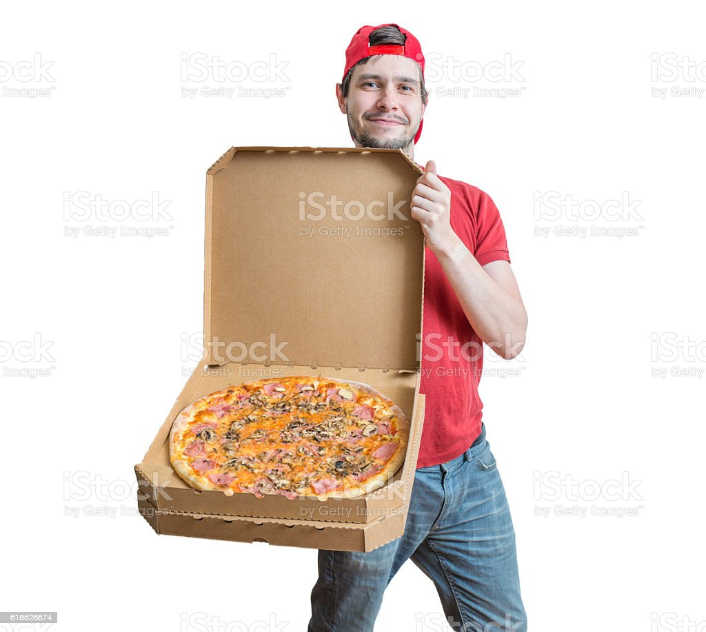 Pizza delivery concept. Young smiling guy is delivering tasty pizza. stock photo