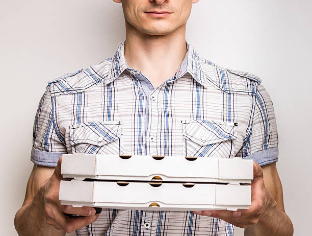 Pizza delivery courier in shirt Pizza delivery courier in shirt holding two boxes with pizza sergionicr stock pictures, royalty-free photos & images