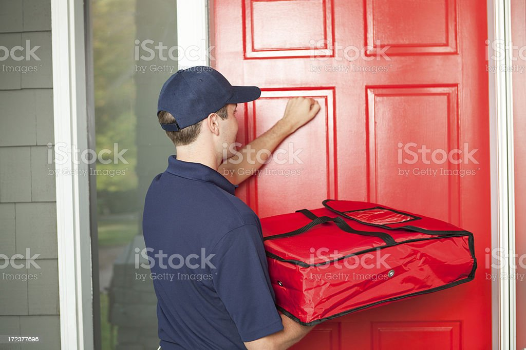 Pizza Delivery Man Delivering Food Package to Customer's Door Hz stock photo