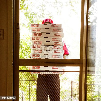 A pizza man making a home delivery holding a stack of pizza boxes.