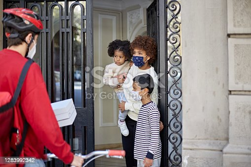 Young single mother in protective mask with son and daughter aged 7 and 3 taking delivery of pizza from bicycle messenger at front door of apartment building.