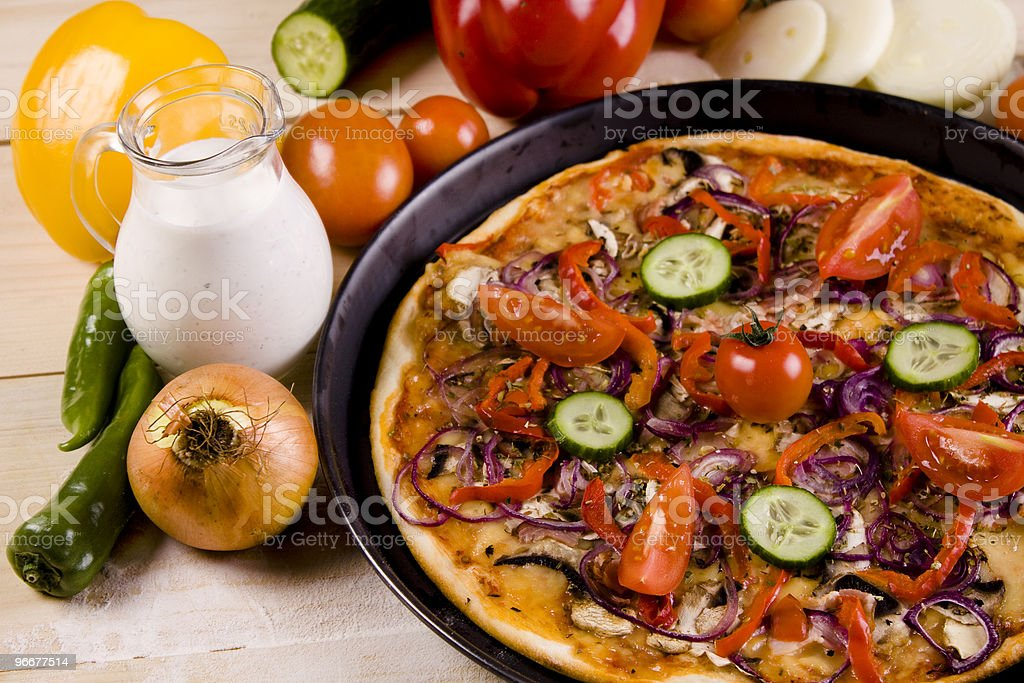Pizza dish on wood floor with tomatos royalty-free stock photo