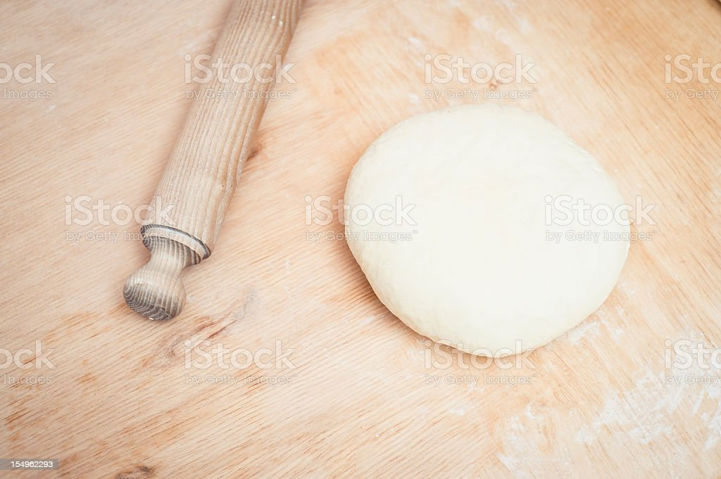 Pizza Dough And Rolling Pin On A Wooden Surface royalty-free stock photo