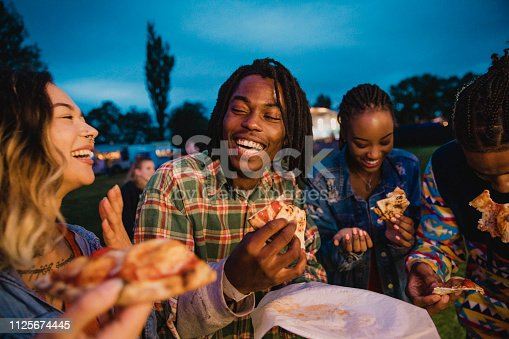 A young group of friends laughing and sharing pizza at a music festival.