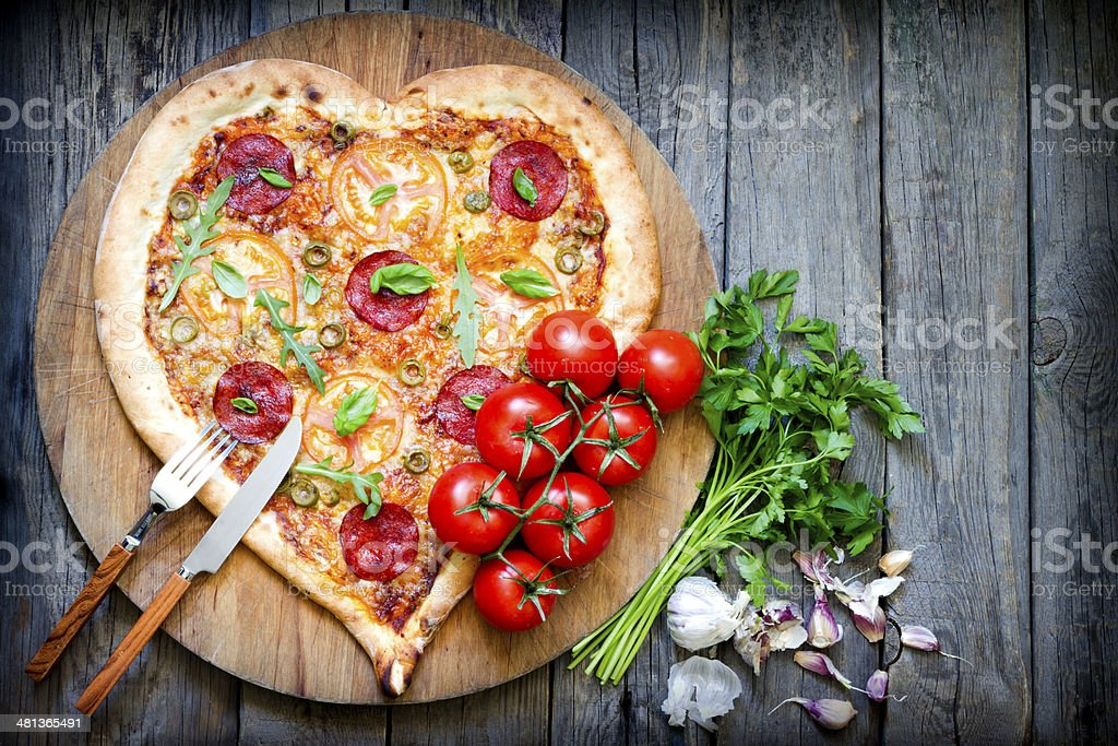 Pizza heart shape with cheese and tomato abstract royalty-free stock photo
