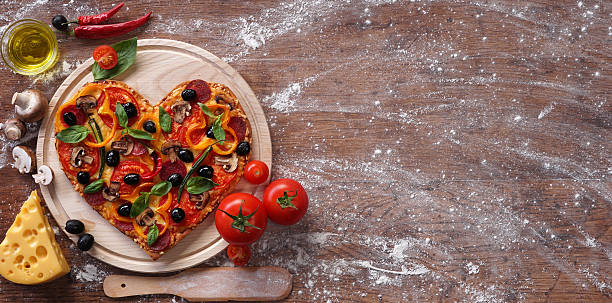 pizza heart shape with ingredients and copy space - pizzeria stock photos and pictures