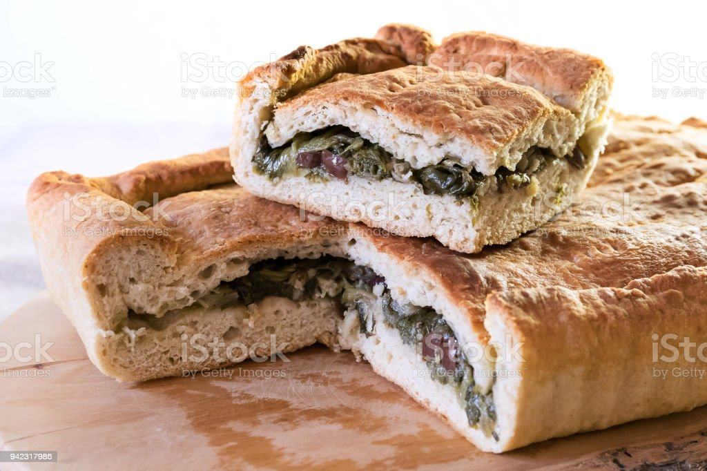 Pizza homemade stuffed with escarole, olives and capers. stock photo