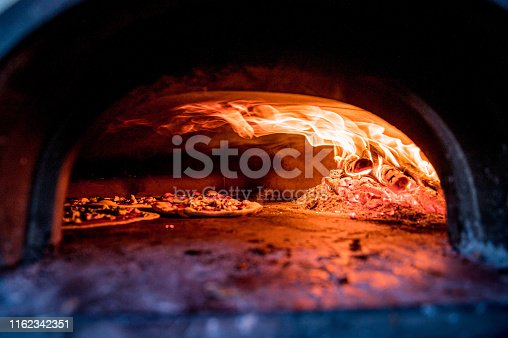 Pizza in pizza oven with fire burning on the inside.