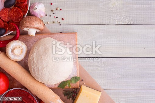 1136817041 istock photo Pizza ingredients and spices on black 1097078790