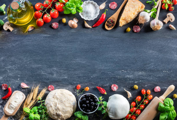 Pizza Ingredients On Black Table In A Raw - Italian Food Ingredients For Making Pizza on Stone Copper Mortar With dough Fresh Basil, Olive Oil, Garlic, Tomato, And Mozzarella ingredient stock pictures, royalty-free photos & images