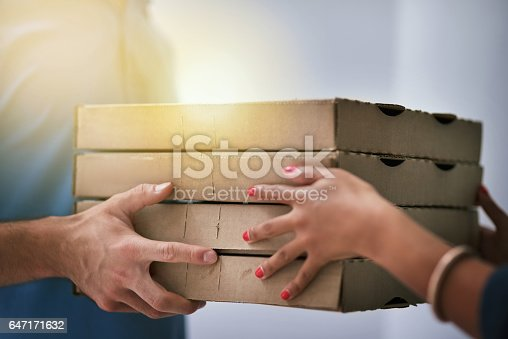 Shot of an unidentifiable businesswoman accepting a pizza delivery from a delivery man in the office
