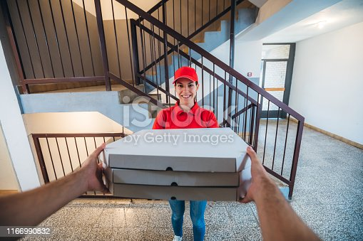 Pizza delivery woman in red cap, t-shirt giving pizza boxes to a customer. Delivery service concept.