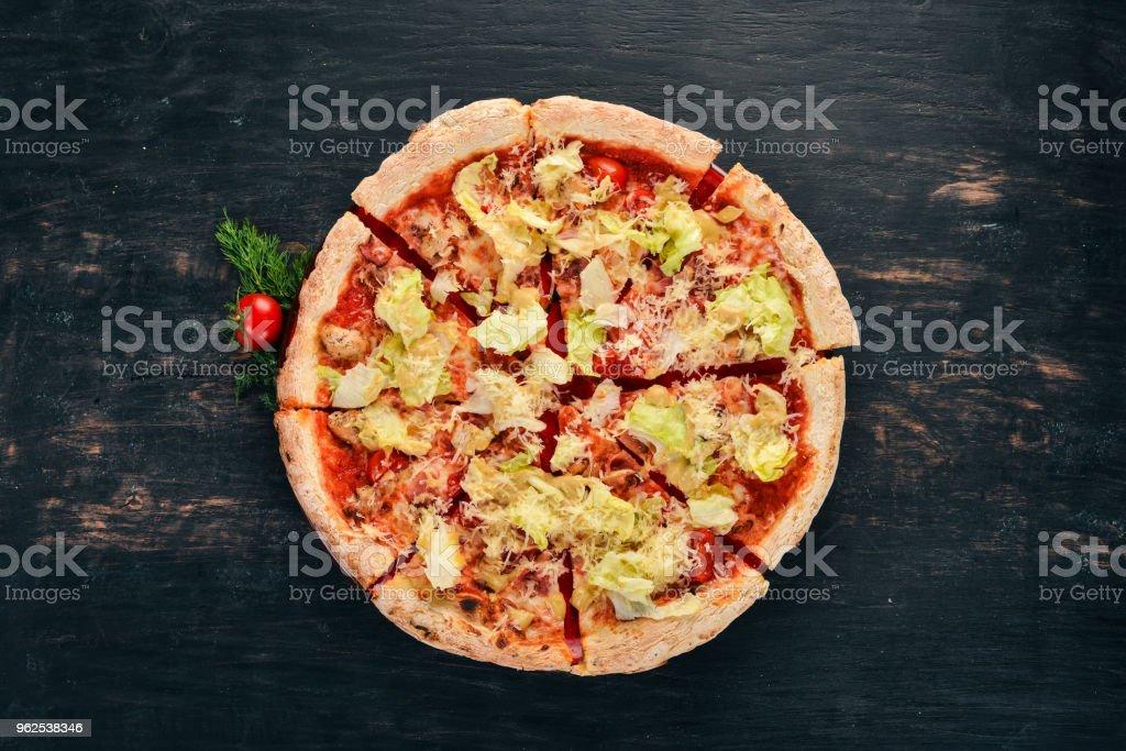 Pizza. Cozinha italiana. Vista superior. Sobre um fundo preto de madeira. Copie o espaço. - Foto de stock de Amarelo royalty-free