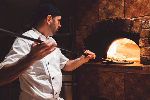 Pizza maker sliding the pizza of a peel in a wood fired oven stock photo