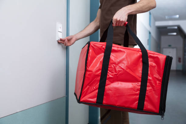 pizza man ringing the door bell with a large bag - food delivery imagens e fotografias de stock