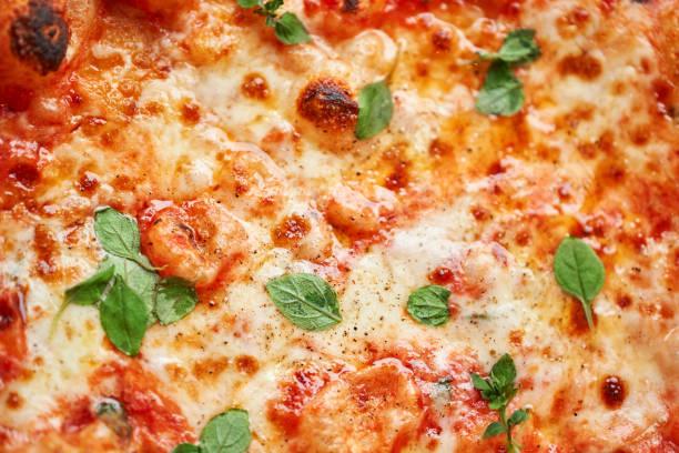 Pizza Margarita. Baked tasty margherita pizza in Traditional wood oven in Neapolitan restaurant, Italy. stock photo
